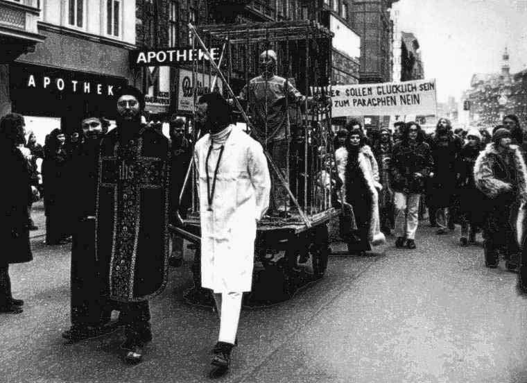 Kunstaktion von Erika Mis 1972: Aus Protest gegen den § 144 ließ sie sich an einem Einkaufssamstag, eingesperrt in einen Käfig, von drei als Richter, Priester und Arzt verkleideten Männern in Sträflingskleidung auf einem Schandkarren durch die Wiener Mariahilfer Straße ziehen. Am Ende zertrümmerte sie in einem symbolischen Akt der Selbstbefreiung ihren Käfig mit einer Axt. Foto: StBKA, © Walter Henisch